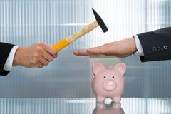 Geschäftsmanneinsparung piggybank vom Hämmern Lizenzfreie Stockfotos