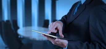 Geschäftsmannerfolg, der mit Tablet-Computer seine Chefetage bearbeitet Stockfoto