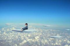 Geschäftsmannfliegen auf Papierflugzeug Lizenzfreie Stockfotos
