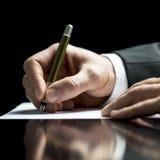 Geschäftsmannschreiben auf einem Blatt des Weißbuches Stockfotografie