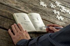 Geschäftsmannschreiben in einem Motivbuch Stockfotografie