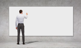 Geschäftsmannschreiben mit Markierung auf weißem Brett Stockbild