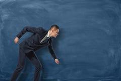 Geschäftsmannstellung, als ob er sein Ziel auf dem blauen Tafelhintergrund laufen lassen oder ausüben wird Lizenzfreie Stockfotos