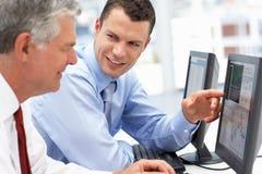 Geschäftsmänner, die an Computern arbeiten Stockbild