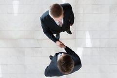 Geschäftsmänner, die Hände im Büro rütteln Stockbilder