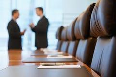 Geschäftsmänner, die im Konferenzsaal sprechen Lizenzfreie Stockfotos