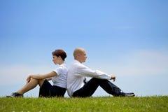 Geschäftspaare, die zurück zu Rückseite auf Gras sitzen Stockfoto