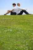 Geschäftspaare, die zurück zu Rückseite auf Gras sitzen Lizenzfreies Stockbild