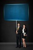 Geschäftspaare mit blauem Brett Stockfoto