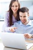 Geschäftspaare unter Verwendung des Laptops Stockfoto