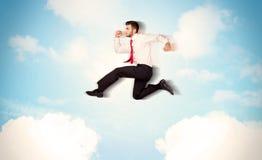 Geschäftsperson, die über Wolken im Himmel springt Stockfotografie