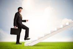 Geschäftsperson, die oben auf weißem Treppenhaus in der Natur klettert Lizenzfreies Stockfoto