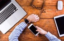 Geschäftsperson, die am Schreibtisch trägt intelligente Uhr arbeitet Stockfoto