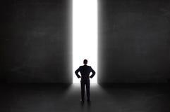 Geschäftsperson, die Wand mit heller Tunnelöffnung betrachtet Lizenzfreie Stockfotos