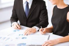 Geschäftsteam auf Sitzung Grafiken besprechend Stockbilder