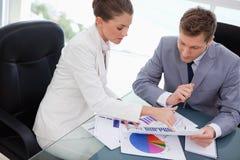 Geschäftsteam, das Marktforschungsergebnisse analysiert Lizenzfreie Stockfotografie