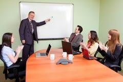 Geschäftsteam motiviert vom positiven Vorführer Lizenzfreie Stockfotos