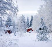 Geschichte des Winters. Rotes finnisches Häuschen Stockfotografie