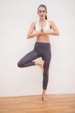 Geschikt brunette die yoga thuis doen Royalty-vrije Stock Afbeelding