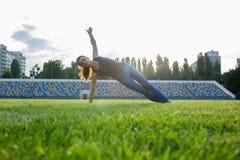 Geschikt donkerbruin meisje in sportkleding die zijou van de plankoefening doen royalty-vrije stock fotografie