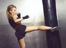 Geschikt en sportief jong meisje die een kickboxing opleiding hebben Ondergrondse gymnastiek Gezondheid, sport, fitness concept Stock Foto's