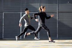 Geschikt en sportief paar die in de straat lopen royalty-vrije stock fotografie