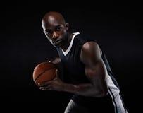 Geschikt jong mannelijk atleten speelbasketbal Royalty-vrije Stock Afbeeldingen