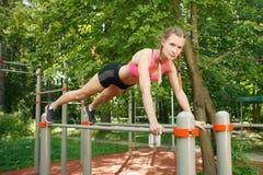Geschikt meisje die oefeningsduw UPS op sportenbars doen openlucht royalty-vrije stock fotografie