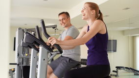 Geschikt sportief positief paar die op hometrainers bij gymnastiek uitwerken Het spreken het flirten met elkaar stock video
