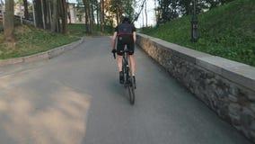 Geschikte atletische fietser die bergop sprinten Volg schot Sterke beenspieren die pedalen draaien Het cirkelen van hard opleidin stock footage
