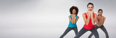 Geschikte atletische vrouwen met grijze achtergrond die oefening doen royalty-vrije stock afbeelding