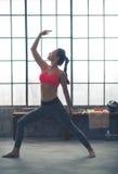 Geschikte blootvoetse vrouw die in profiel yogarek in zoldergymnastiek doen Royalty-vrije Stock Foto's