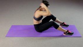 Geschikte dame met ideaal lichaam die buikkraken, de vlakke routine van de buiktraining doen stock video