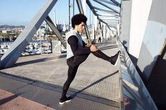 Geschikte en sportieve jonge mens die het uitrekken in stad doen zich royalty-vrije stock afbeeldingen