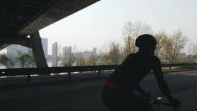 Geschikte en sterke fietser die een fiets met stad, brug en rivier op achtergrond pedaling Het cirkelen concept en opleiding stock videobeelden