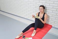 Geschikte gezonde vrouw die in sportkleding een verse salade na geschiktheidstraining eten royalty-vrije stock foto