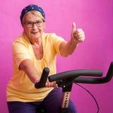 Geschikte hogere vrouw die duimen omhoog op fiets doen Stock Foto's