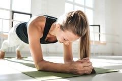 Geschikte jonge atletische vrouwelijke het doen planktraining om haar abs in zonnige witte gom in de ochtend te verbeteren stock afbeeldingen