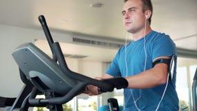Geschikte jonge mens die in gymnastiek oefeningen op velosimulator doen Het luisteren muziek op smartphone met oortelefoons stock footage