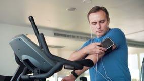 Geschikte jonge mens die in gymnastiek oefeningen op velosimulator doen Het luisteren muziek op smartphone met oortelefoons stock videobeelden