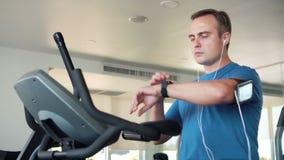 Geschikte jonge mens die in gymnastiek oefeningen op velosimulator doen Het luisteren muziek op smartwatch met oortelefoons stock video