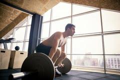 Geschikte jonge mens die met een barbell bij de gymnastiek uitwerken Bodybuilderwijfje die bij de gymnastiek uitoefenen Stock Afbeelding