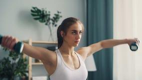 Geschikte jonge sportvrouw opleiding met dumb-bells die thuis van gewichtheffen genieten stock video