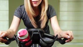 Geschikte jonge vrouw die fiets met behulp van bij de gymnastiek Sterke vrouwelijke atleet die cardiotraining op cyclus doen bij  stock video