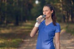 Geschikte jonge vrouw die gebotteld water drinken royalty-vrije stock fotografie