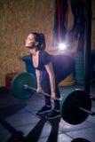 Geschikte jonge vrouw die met een barbell bij de gymnastiek uitwerken Bodybuilderwijfje die bij de gymnastiek uitoefenen Royalty-vrije Stock Fotografie