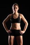 Geschikte jonge vrouw die zich in zwarte sportenuitrusting bevindt royalty-vrije stock foto