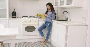 Geschikte jonge vrouwelijke gebruikende telefoon in keuken stock videobeelden