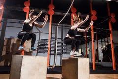 Geschikte jonge vrouwendoos die bij een dwars geschikte gymnastiek springen stock afbeeldingen