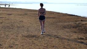 Geschikte jonge vrouwenjogging langs een zandig strand stock footage